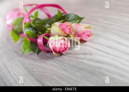 Pink roses on a wooden table - Stock Photo