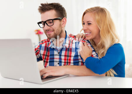 Happy couple browsing something on laptop - Stock Photo