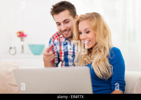Man showing something on computer his girlfriend - Stock Photo