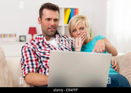 Young couple watching something on their laptop - Stock Photo