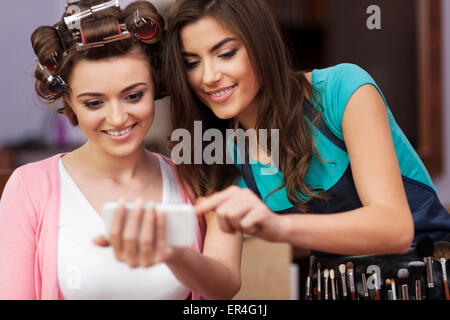 Makeup artist and female customer looking on mobile phone. Debica, Poland - Stock Photo