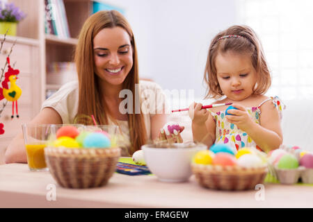 Focus little girl painting easter eggs with her mother. Debica, Poland - Stock Photo