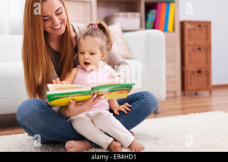 Beautiful mother showing images in a book to her cute little girl. Debica, Poland - Stock Photo