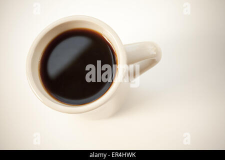 White cup full of black coffee stands on the table with soft shadow. Top view, soft shadow, vintage photo filter - Stock Photo