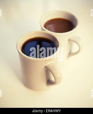 Two cups full of coffee stand on the table with soft shadow, vintage stylized photo filter with old style effect - Stock Photo
