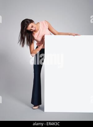 Happy elegant woman peeking on whiteboard. Debica, Poland - Stock Photo