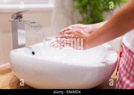 Close up of woman washing hands in bathroom. Debica, Poland - Stock Photo