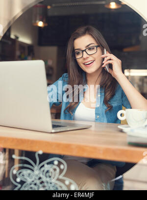Happy woman talking by mobile phone and using laptop at cafe. Krakow, Poland - Stock Photo