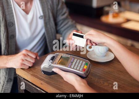 Close up of customer paying by credit card. Krakow, Poland - Stock Photo