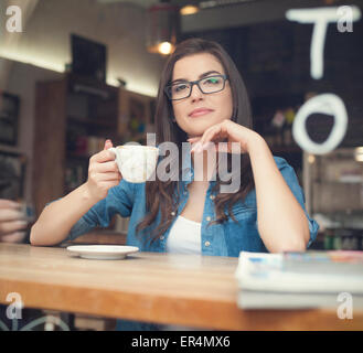 Portrait of beautiful woman drinking coffee at cafe. Krakow, Poland - Stock Photo