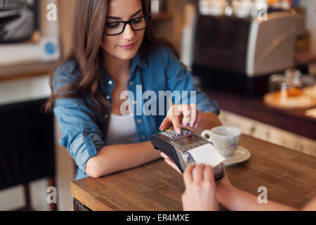 Young woman paying for cafe by credit card reader. Krakow, Poland - Stock Photo