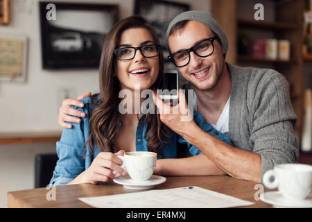 Happy young couple listening voice from mobile phone. Krakow, Poland - Stock Photo