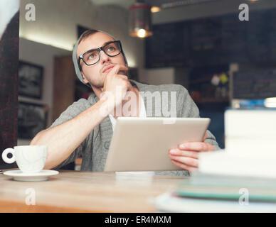 Dreaming man using digital tablet at cafe. Krakow, Poland - Stock Photo