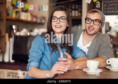 Hipster couple talking with friends at cafe. Krakow, Poland - Stock Photo