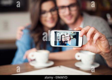 Loving couple taking selfie at cafe. Krakow, Poland - Stock Photo