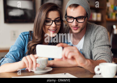 Hipster couple using mobile phone at cafe. Krakow, Poland - Stock Photo