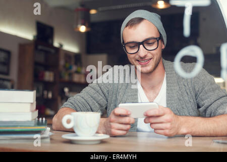 Hipster man with mobile phone at cafe. Krakow, Poland - Stock Photo