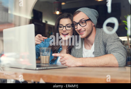Couple have fun while looking on laptop at cafe. Krakow, Poland - Stock Photo