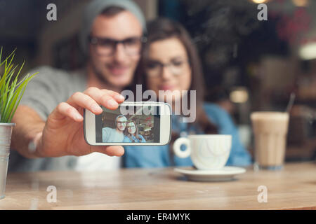Hipster couple taking selfie at cafe. Krakow, Poland - Stock Photo