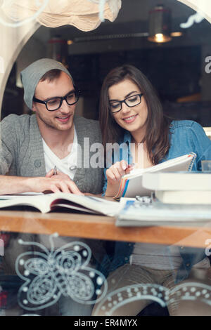 Hipster couple studying together at cafe. Krakow, Poland - Stock Photo
