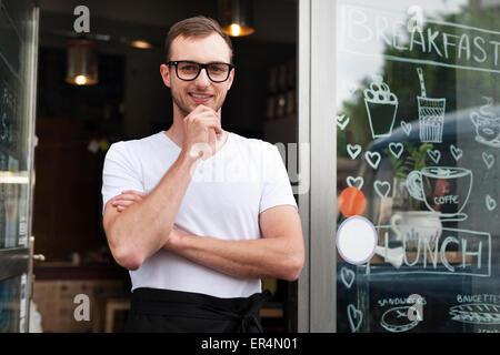 Portrait of smiling male waiter outside the cafe. Krakow, Poland - Stock Photo