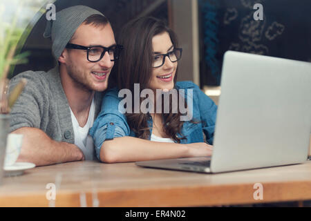 Stylish couple with contemporary laptop in cafe. Krakow, Poland - Stock Photo