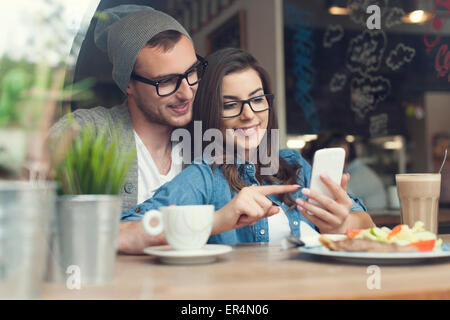 Embracing couple using mobile phone in cafe. Krakow, Poland - Stock Photo