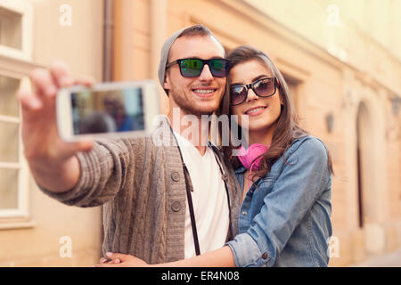 Fashionable couple taking selfie by mobile phone. Krakow, Poland - Stock Photo