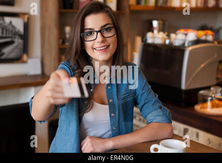 Smiling woman paying for coffee by credit card. Krakow, Poland - Stock Photo