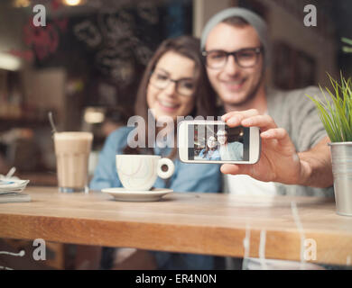 Catching memories by stylish young couple. Krakow, Poland - Stock Photo