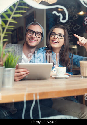 Happy couple using digital tablet at cafe. Krakow, Poland - Stock Photo