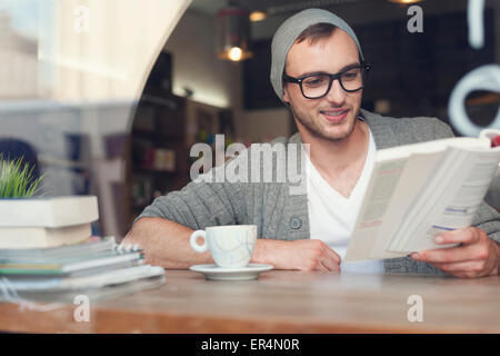 Smiling hipster man reading book at cafe. Krakow, Poland - Stock Photo