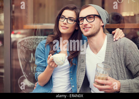 Young fashion couple drinking coffee outside of cafe. Krakow, Poland - Stock Photo