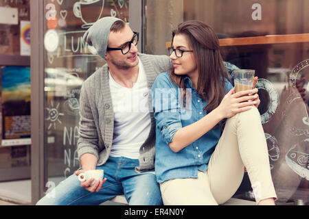 Young people relaxing with cup of coffee outside the cafe. Krakow, Poland - Stock Photo