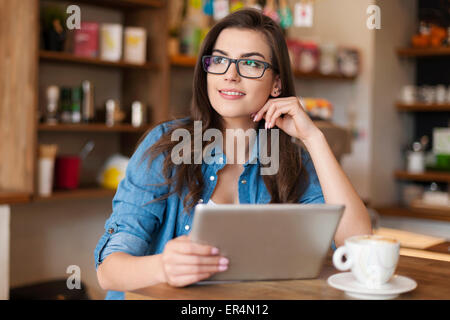 Thoughtful young woman using digital tablet at cafe. Krakow, Poland - Stock Photo