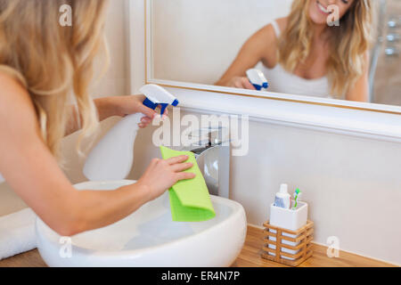 Blonde young woman cleaning bathroom. Debica, Poland - Stock Photo