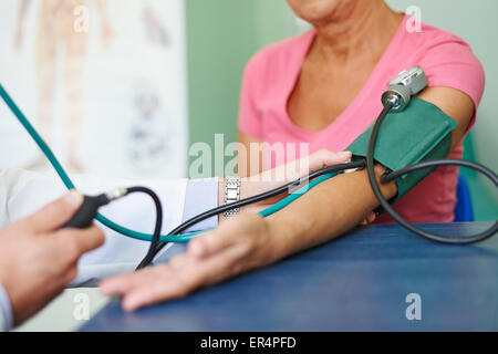 Doctor measures pressure in senior patient. Debica, Poland - Stock Photo