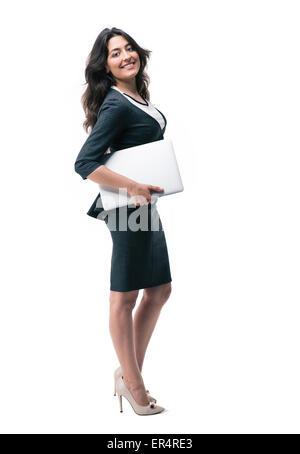 Full length portrait of a happy businesswoman standing with laptop isolated on a white background. Looking at camera - Stock Photo