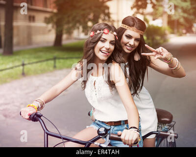 Portrait of funny boho girls on a tandem bicycle. Krakow, Poland - Stock Photo