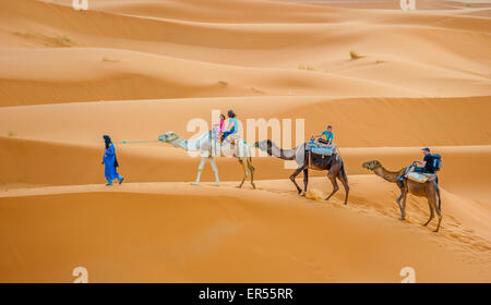ERG CHEBBY, MOROCCO - April, 12, 2013: Tourists riding camels in Erg Chebbi, Morocco - Stock Photo