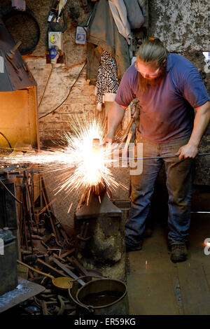 a blacksmith at work in his forge in southsea england uk - Stock Photo