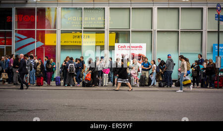 Travelers wait to board an inter-city bus in New York on Friday, May 22, 2015 to escape the city over the Memorial - Stock Photo