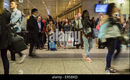 Travelers for the LIRR in Penn Station in New York on Friday, May 22, 2015 wait for their trains to board to escape - Stock Photo