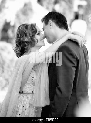 Newly wed couple kissing outdoor on a summer day. - Stock Photo