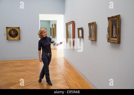 Woman explaining artwork in the Georg Schaefer Museum, Schweinfurt, Franconia, Bavaria, Germany - Stock Photo