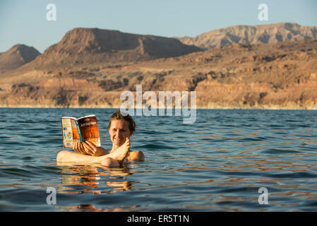 Woman reading a guidebook in Dead Sea, Jordan, Middle East - Stock Photo