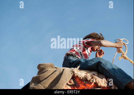 Young man riding a camel and smoking a cigarette, Petra, Jordan, Middle East - Stock Photo