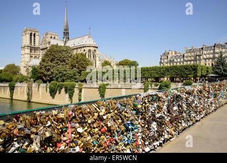 Love padlocks on bridge Pont de L'Archeveche in front of cathedral Notre Dame, Paris, France, Europe - Stock Photo