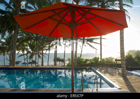 Parasol and pool under palm trees with sea view, Turtle Bay Hotel, Tangalle, South Sri Lanka - Stock Photo