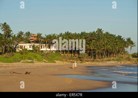 Two tourists on a deserted beach, Turtle Bay Hotel in the background, Tangalle, South Sri Lanka - Stock Photo